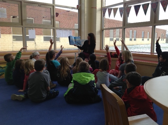 photo of Mrs. Randenburg reading to Mrs. Croxdale's class in library as a reward