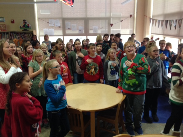 NCE students in Christmas sweaters saying the pledge of allegiance