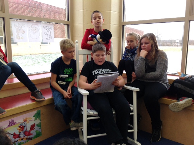 A student reads to his 4th grade classmates during library