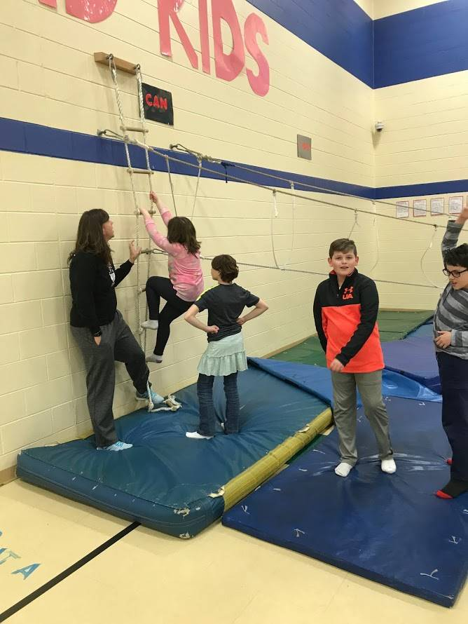 photo of students on climbing equipment in gym class