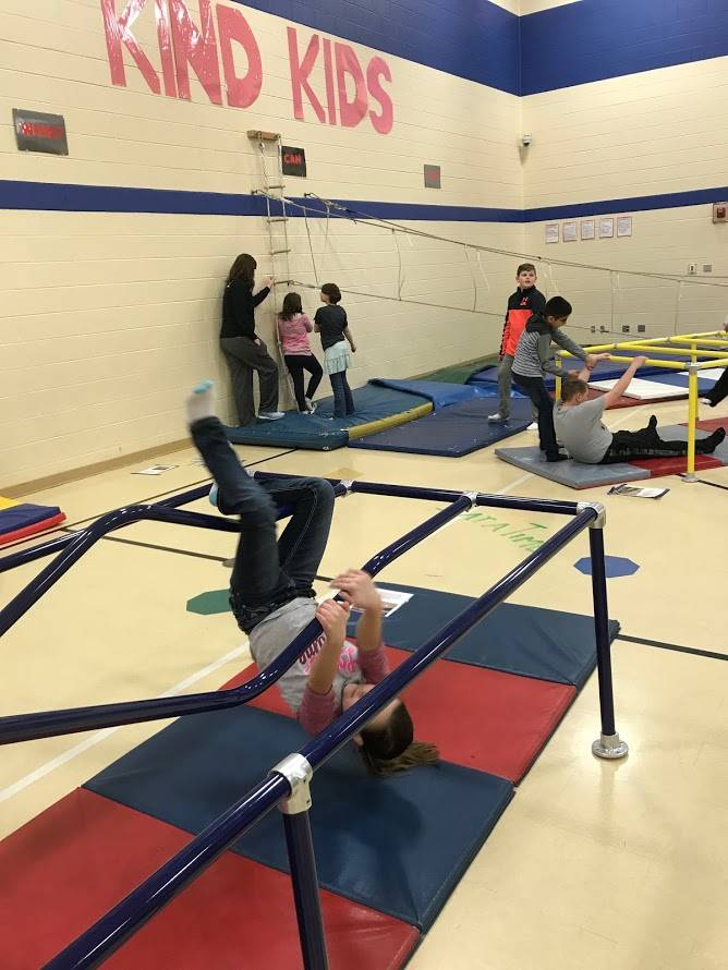 students on climbing equipment in gym class