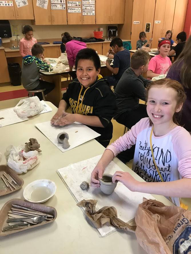 5th graders making coil clay pots in art class
