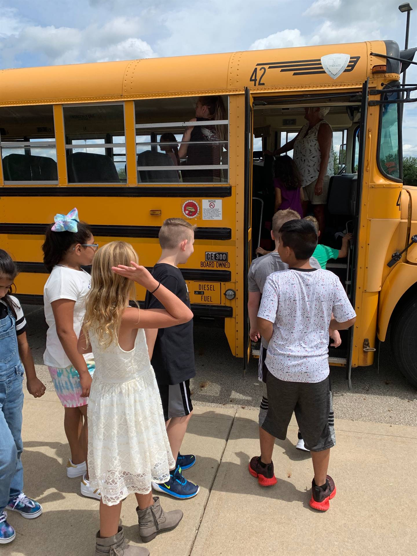 students boarding a school bus NCE fall 2019