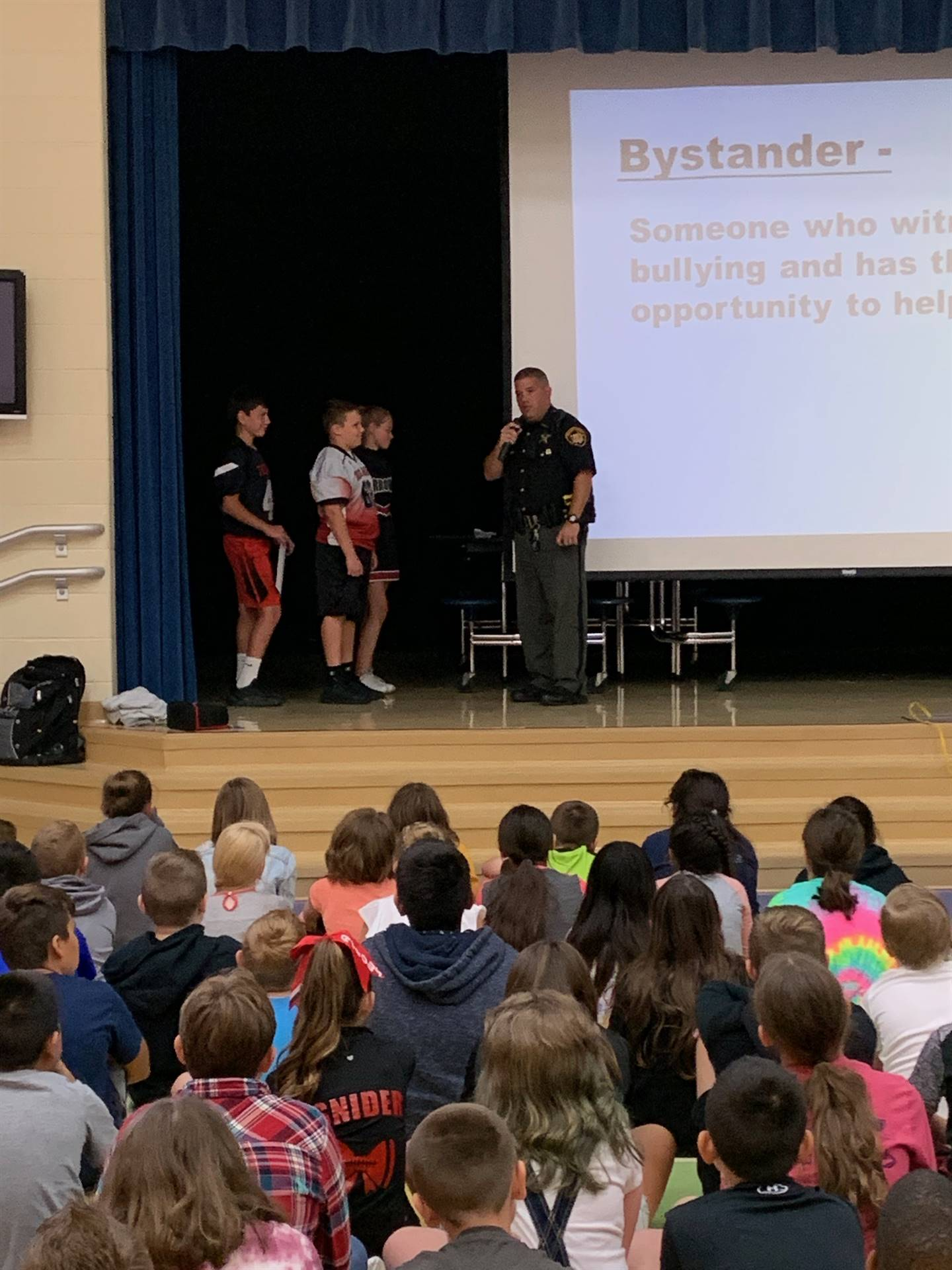 Three 5th grade boys onstage with officer at the anti-bullying assembly at NCE