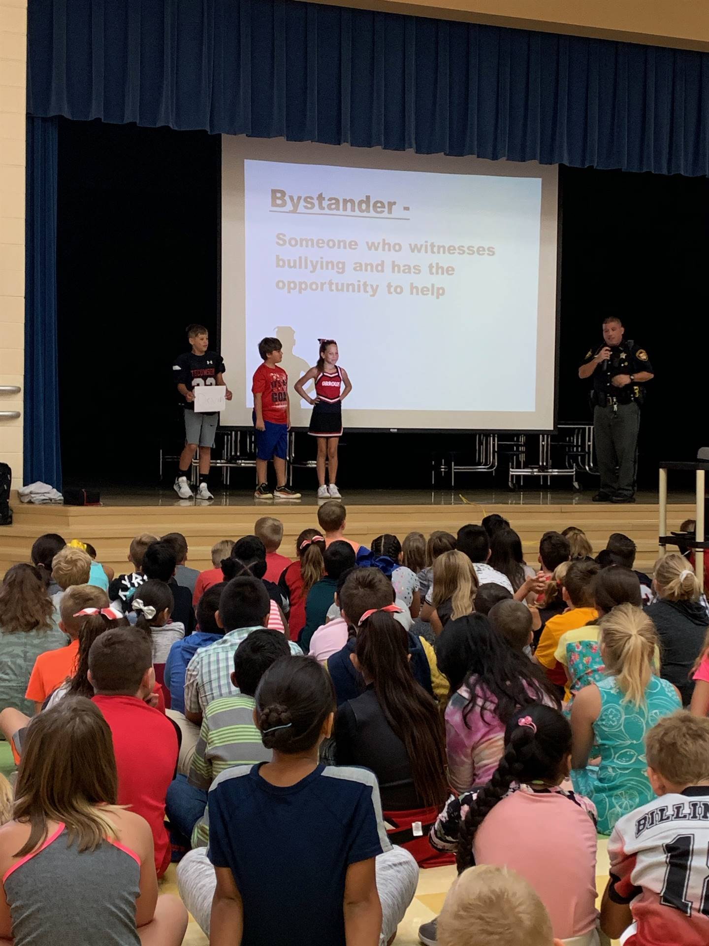 4th grade students on stage with officer at anit-bullying assembly at NCE