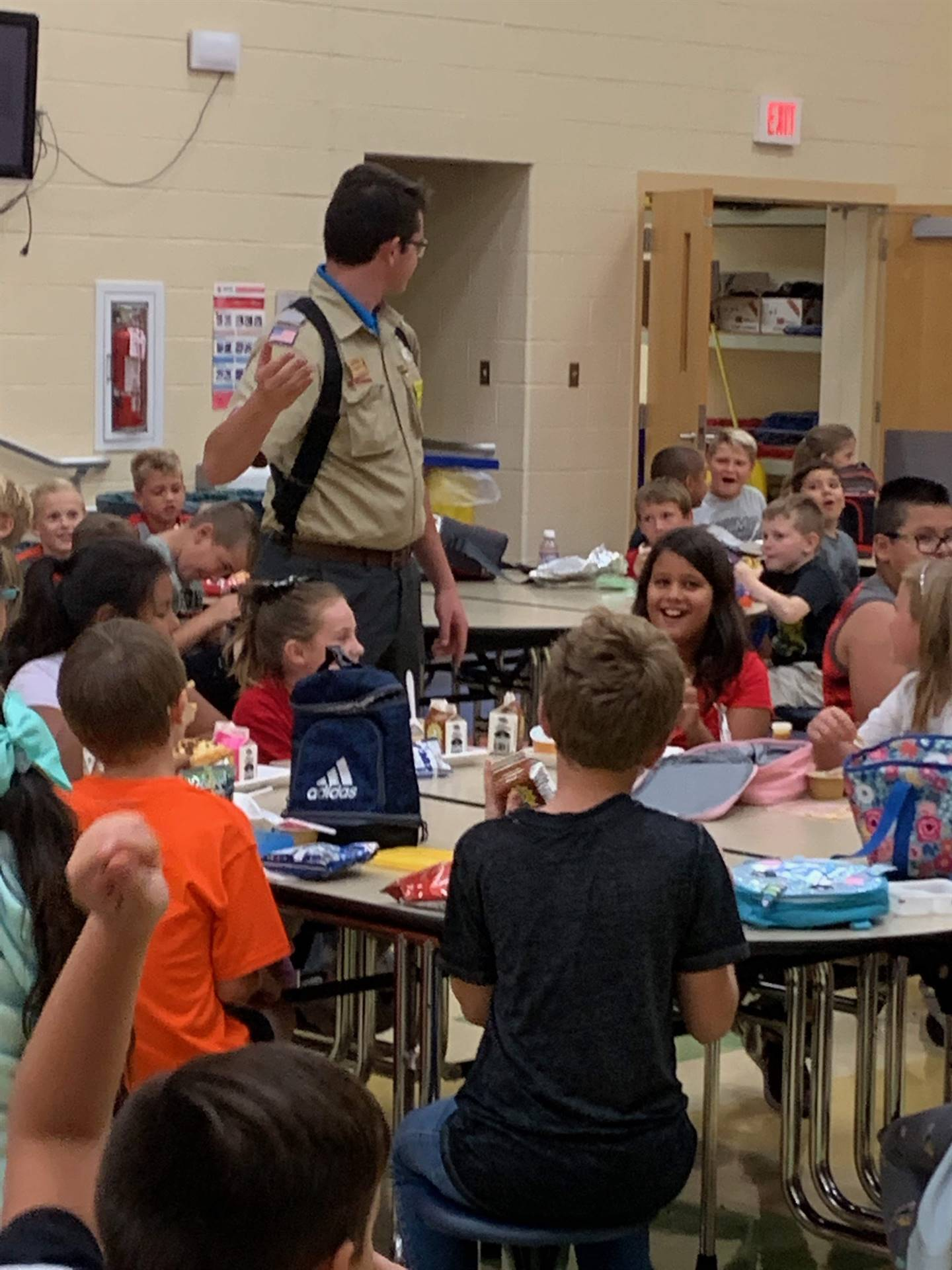Boy Scout leader talking to NCE students in the cafeteria
